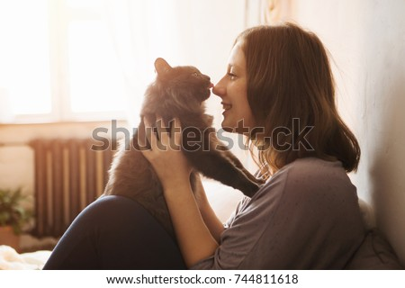 young woman playing with cat in ...
