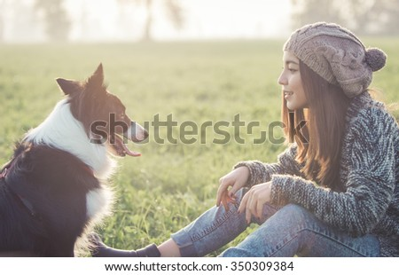 Young woman playing with her border collie dog. concept about animals and people