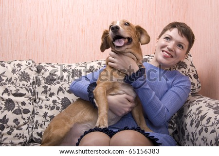 Young woman playing with her dog on sofa in her apartment