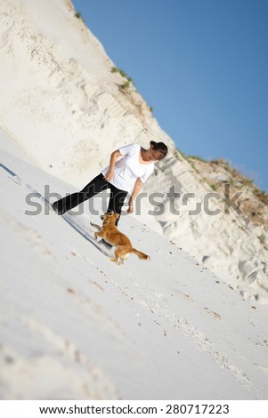 young woman playing with her red dog on white sand. laughing, having fun