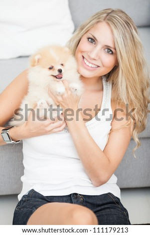 young woman playing with her tinny dog at home