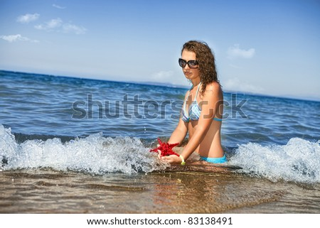 young woman playing with starfish on beach in greece