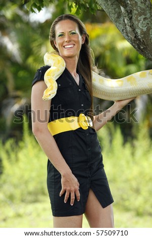 Young woman plays with a albino burmese python