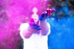 Young woman plays with colors, creating a colour explosion with blue and pink powder. Concept for Indian festival holi