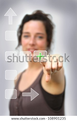 young woman pointing at a digital interface and on a green plus