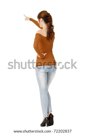 Young woman pointing, full length portrait from back isolated on white background.