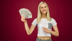 Young woman pointing towards a stack of money with her finger isolated on ruby background - Image