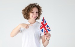 Young woman points to the flag of Great Britain, urging her to learn English.