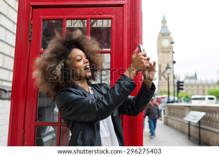 Young woman portrait close to red telephone box in London taking a selfie with smart phone. Big Ben in the background.