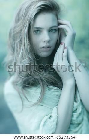 Young woman portrait. Cold aqua blue tint.