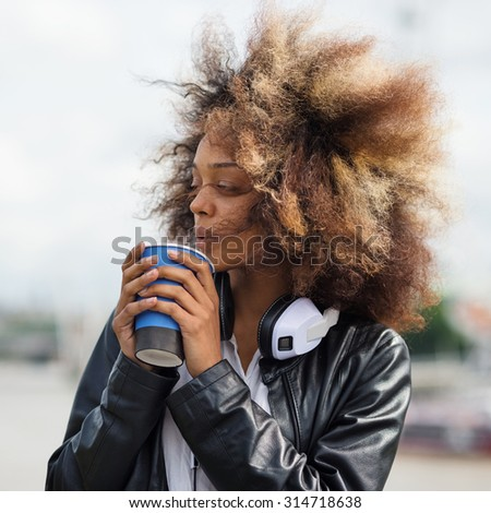 Young woman portrait outdoors on Westminster Bridge in London with coffee cup and headphones.