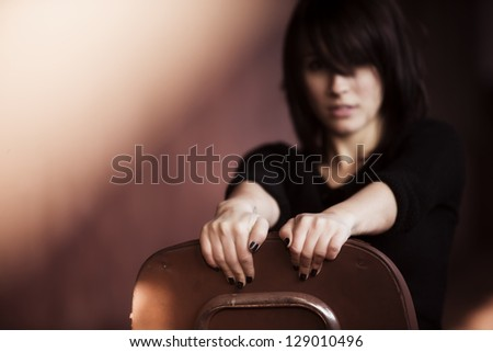 Young woman portrait showing attitude sitting on a chair.
