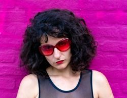 Young woman portrait wearing red sunglasses at a pink brick wall