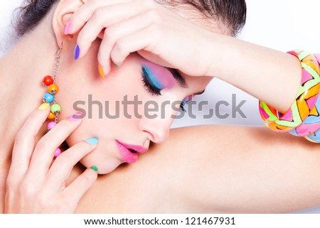 young woman portrait with colorful makeup and nail polish, studio shot