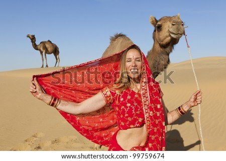 Young woman poses in a saree with camels in the desert, Rajasthan - India
