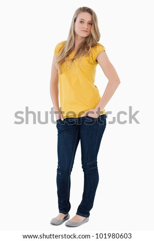 Young woman posing hands in the pockets with a yellow shirt against white background