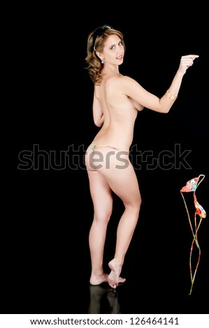 Young woman posing in a string bikini, removing her top and dropping it. - stock photo