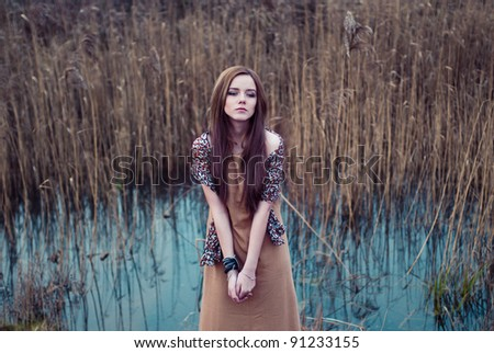 young woman posing next to the water fall