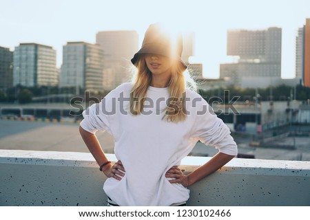 Young woman posing on a rooftop during the sunset with city centre on a background. Blank sweatshirt mock-up.
