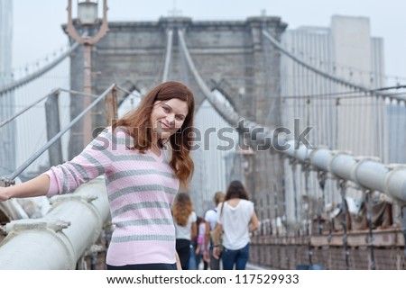 Young woman posing on Brooklyn Bridge with Manhattan in background