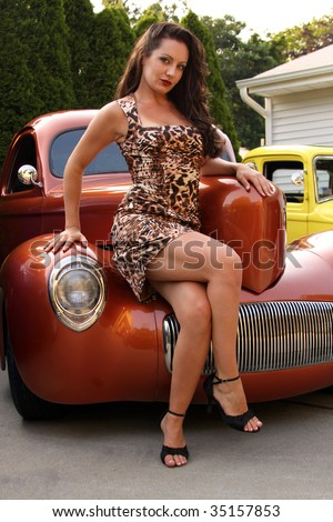 Young woman posing on copper hot rod