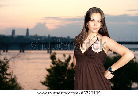 Young woman posing on the sunset panorama of Kiev background