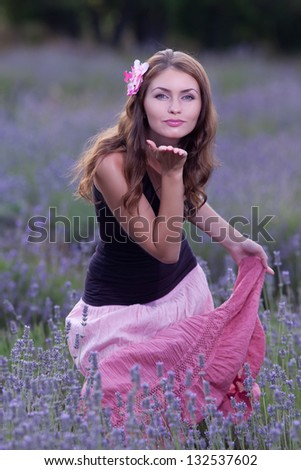 Young woman posing outdoors. Attractive girl in the field of blossoming lavender