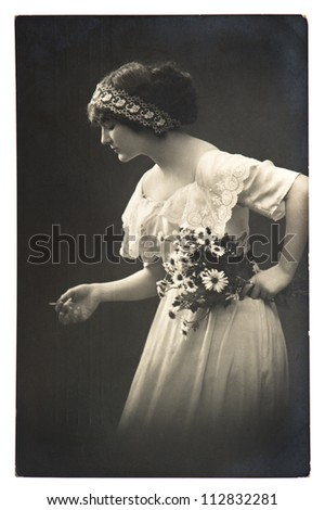 young woman posing with daisy flowers. vintage picture from 1913