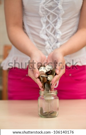 Young woman pouring coins into a jar
