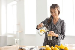 Young woman pouring fresh lemonade from jug into glass at home