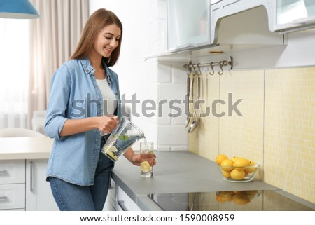 Young woman pouring lemon water into glass in kitchen