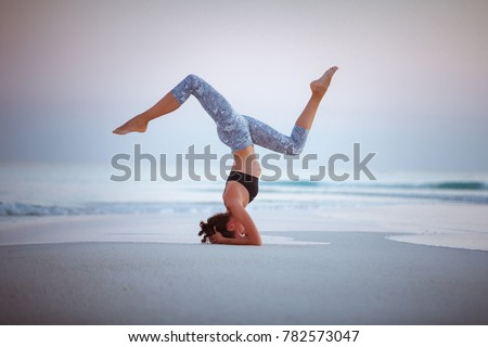 Young woman practice balance asanas on Summer yoga session on a beautiful golden beach of Maldives on a yoga tour, Fulhadhoo, Salamba Sirsasana - supported headstand
