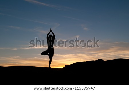 Young woman practices a sun salutation at sunset. Yoga practice and healthy lifestyle. Figure in silhouette