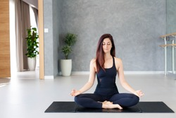 Young woman practices yoga. Girl is doing meditation and exercises on mat indoors. Sport workout in gym. Concept of calmness, relax, healthy lifestyle, wellbeing. Female fitness classes.