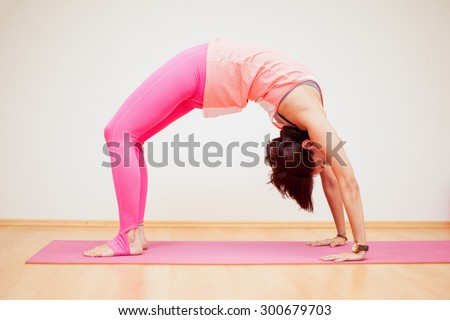 Young woman practicing a backbend yoga pose in a yoga studio