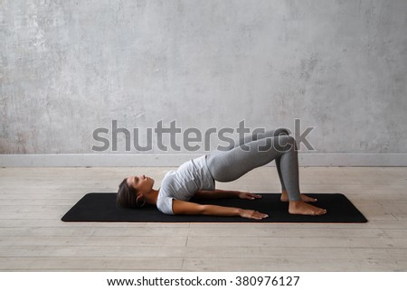 Young woman practicing advanced yoga. Bridge Pose. Setu Bandha Sarvangasana  #380976127