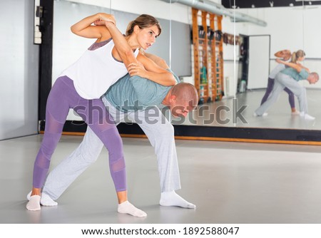 Young woman practicing basic protection skills with man during self defense course in gym Stock fotó ©