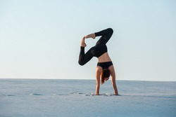 Young woman practicing inversion balancing yoga pose handstand on sand.