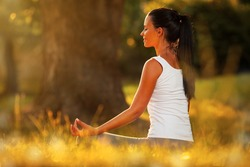 Young woman practicing morning meditation in nature at the park. Health lifestyle concept.