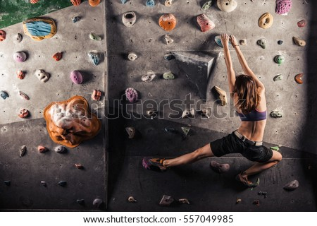 Young woman practicing rock-climbing on a rock wall indoors #557049985