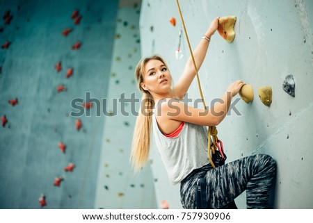 Young woman practicing rock-climbing on a rock wall indoors #757930906