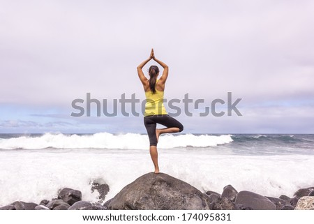 Young woman practicing tree yoga pose near the ocean during sunset