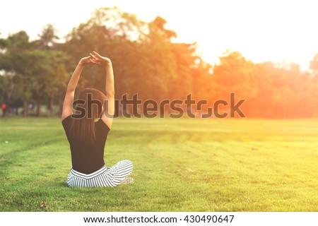 young woman practicing yoga at...