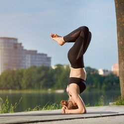 Young woman practicing yoga at city lake. Doing Salamba Sirsasana, supported headstand pose. Leading a healthy lifestyle outdoor, meditation in nature