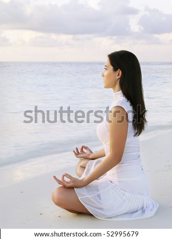 Young woman practicing yoga at sunrise near the ocean