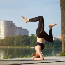 Young woman practicing yoga at urban lake, doing Salamba Sirsasana, supported headstand pose, healthy lifestyle outdoor, modern building on the background
