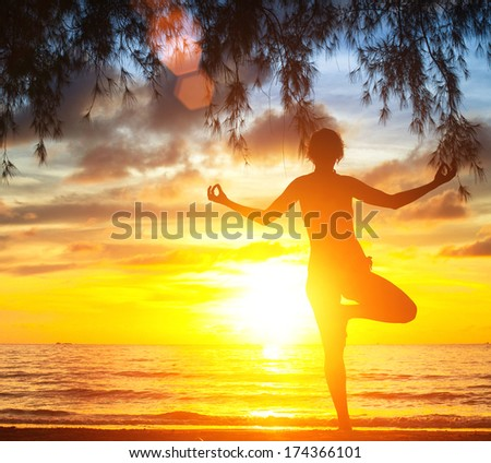 Young woman practicing yoga by the sea beach at sunset.