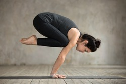 Young woman practicing yoga, doing Crane exercise, Bakasana pose, working out, wearing sportswear, black pants and top, indoor full length, gray wall in yoga studio