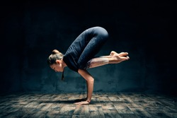 Young woman practicing yoga doing forearm stand crane pose asana in dark room. Bakasana. Wellness and healthy lifestyle