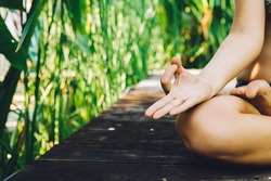Young woman practicing yoga during luxury yoga retreat in Asia, Bali, meditation, relaxation, getting fit, enlightening, green grass jungle background